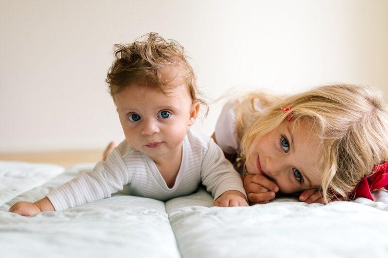 grote-zus-met-baby-broertje-kijken-in-camera-tijdens-fotoshoot